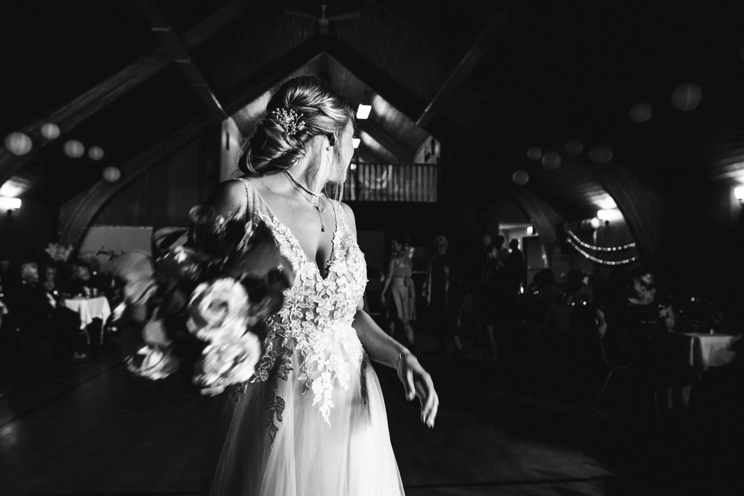 black and white action shot of bride throwing her bouquet and looking over her shoulder