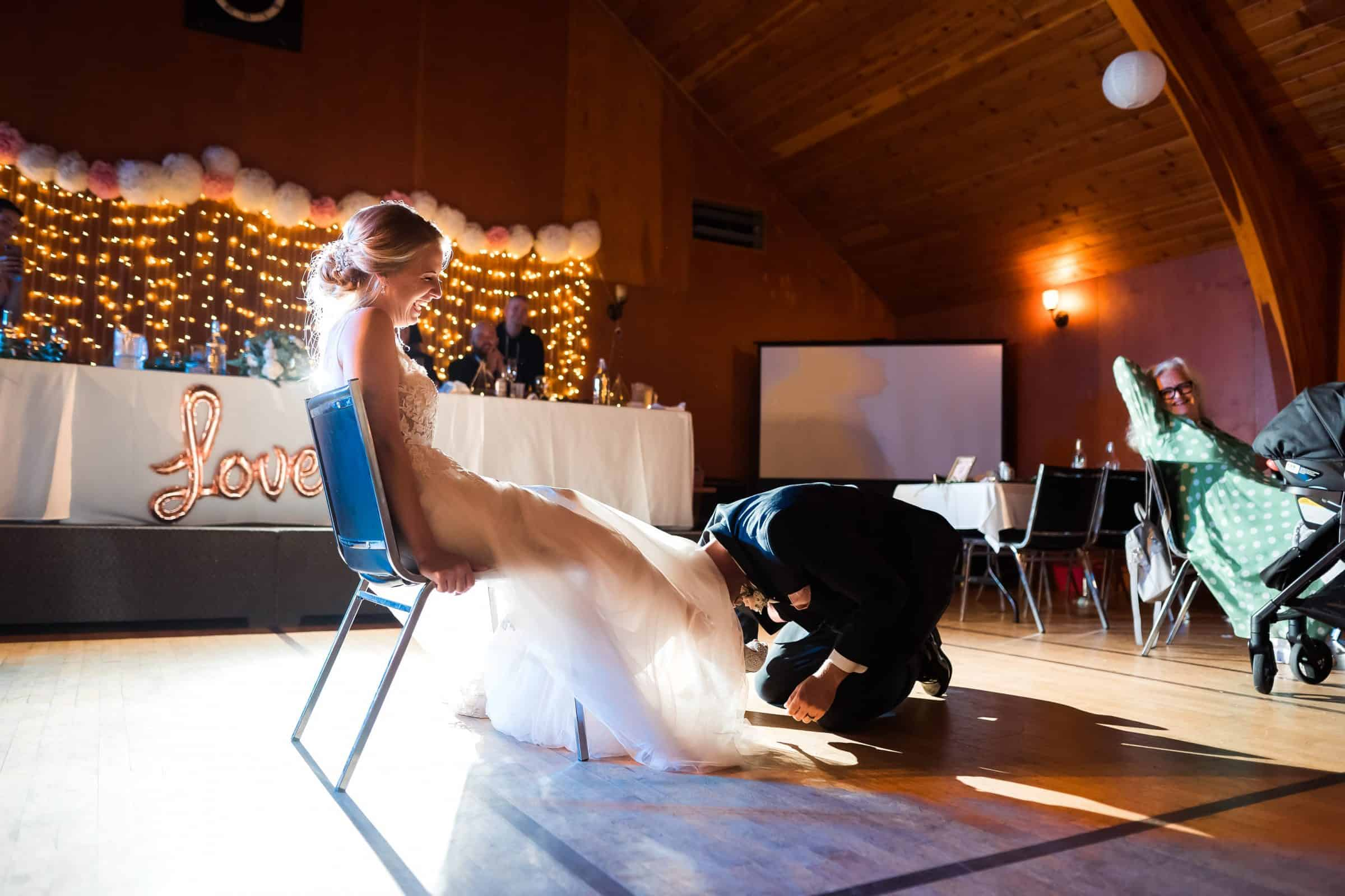 groom going under dress to take off garter while bride laughs