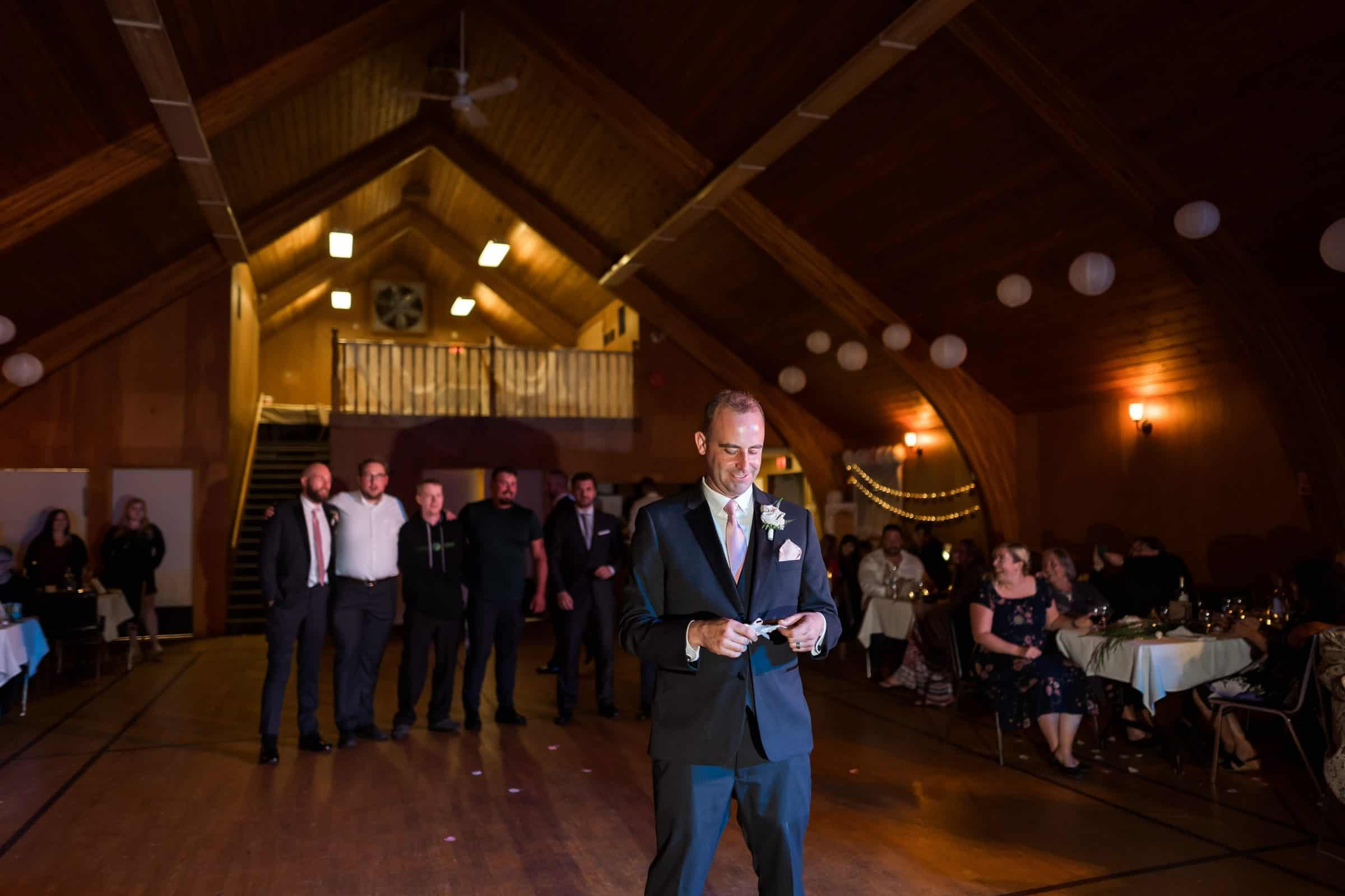 groom getting ready to throw garter with men in the background