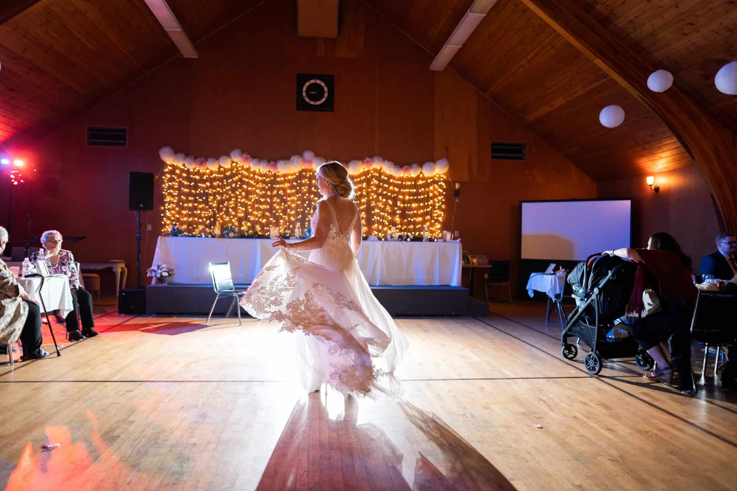 bride twirling with her dress backlit on the dance floor