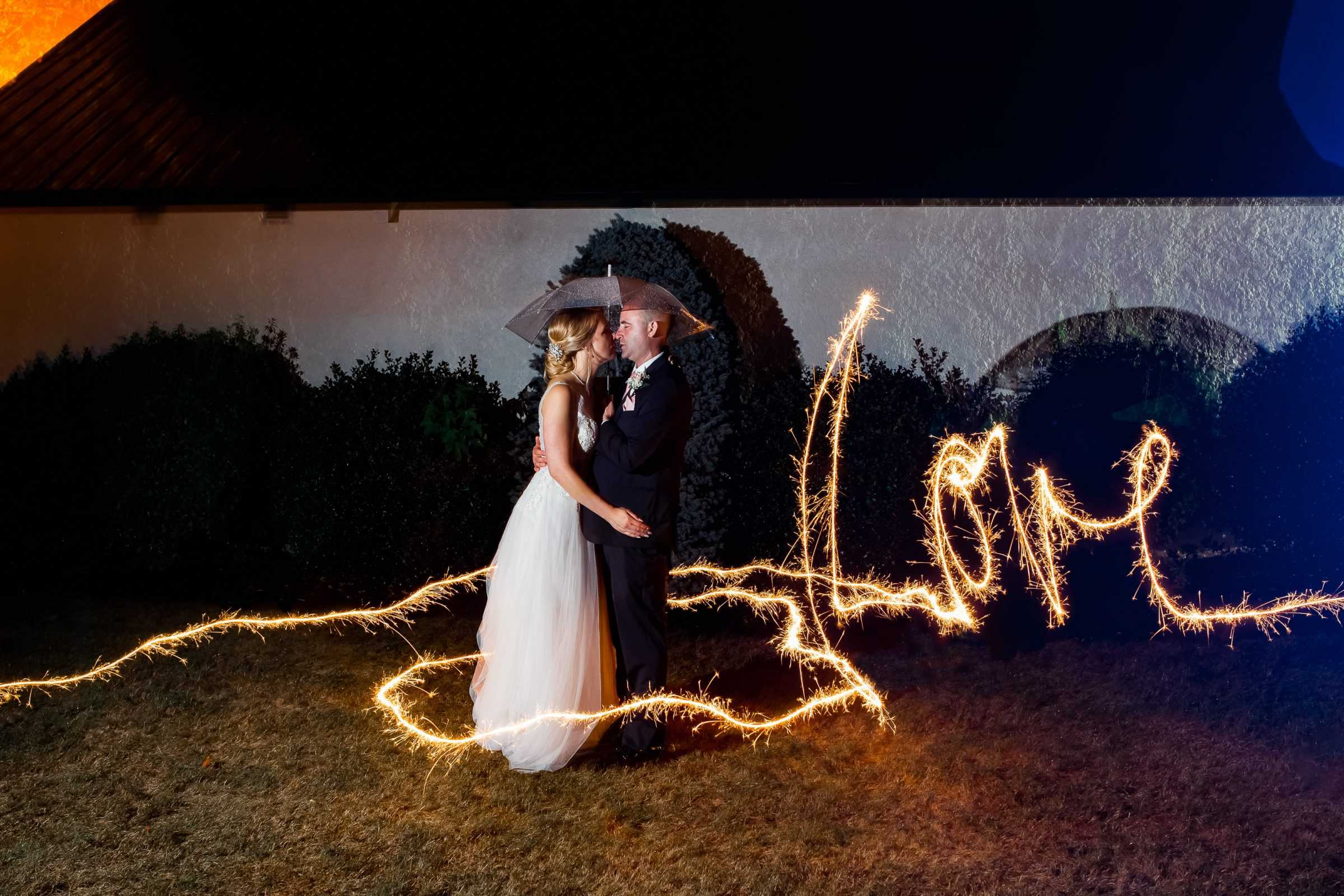 """bride and groom kissing under umbrella with """"love"""" in sparklers"""