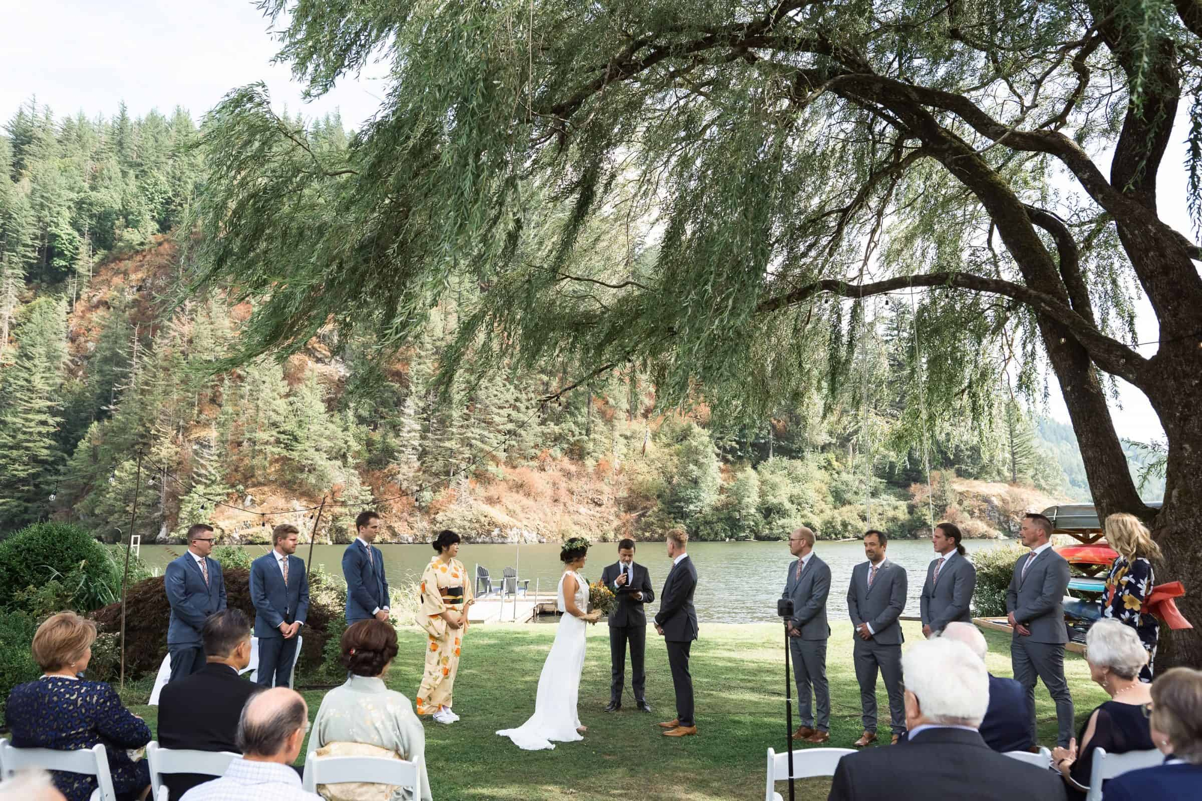 pull back of bride, groom, and wedding party in backyard wedding under willow tree with river in background