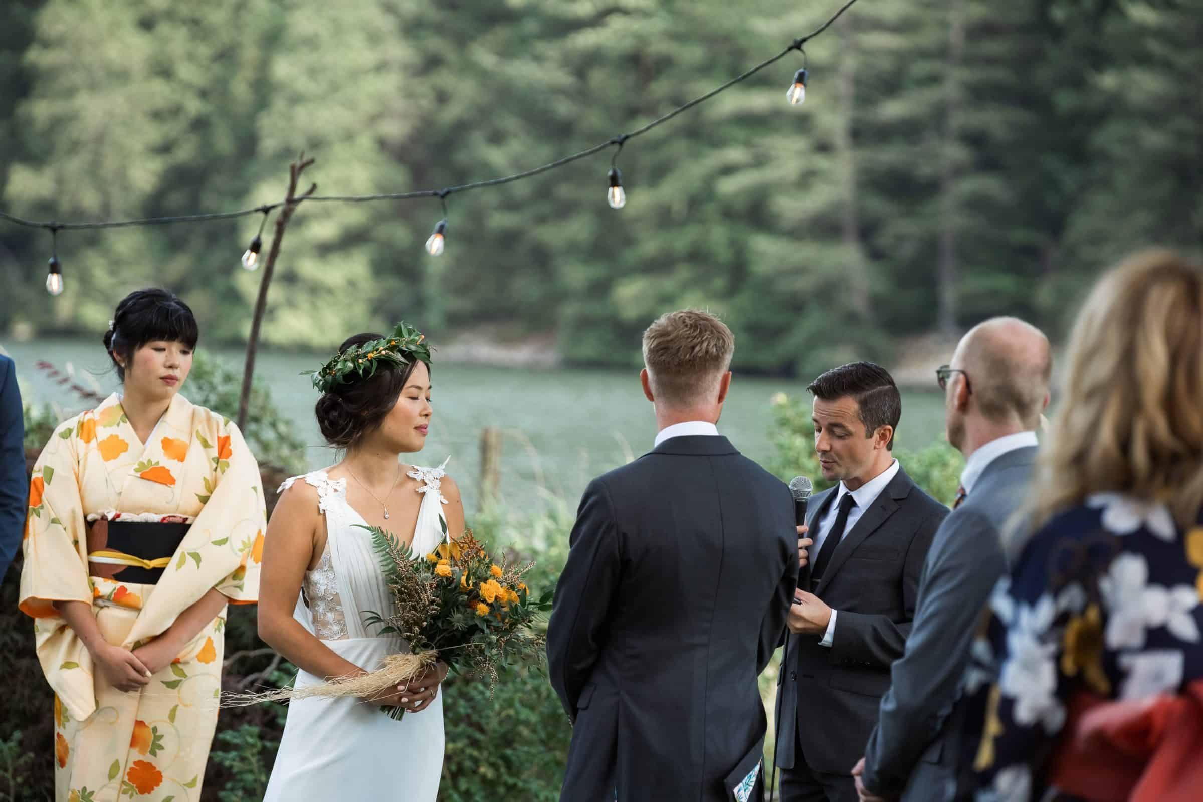 close up of bride, groom, and officiant with river in the background