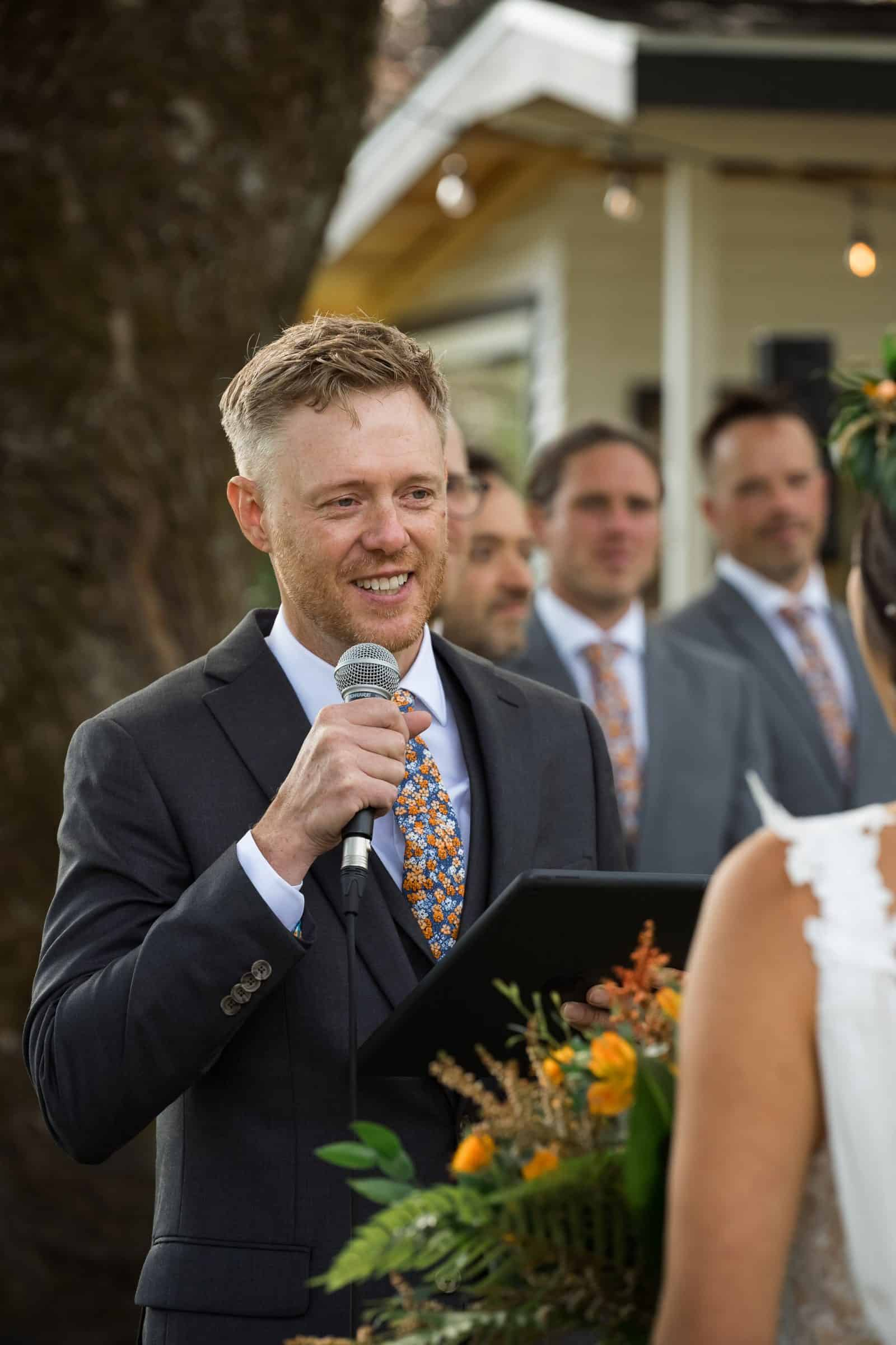 groom reading vows to bride holding mic