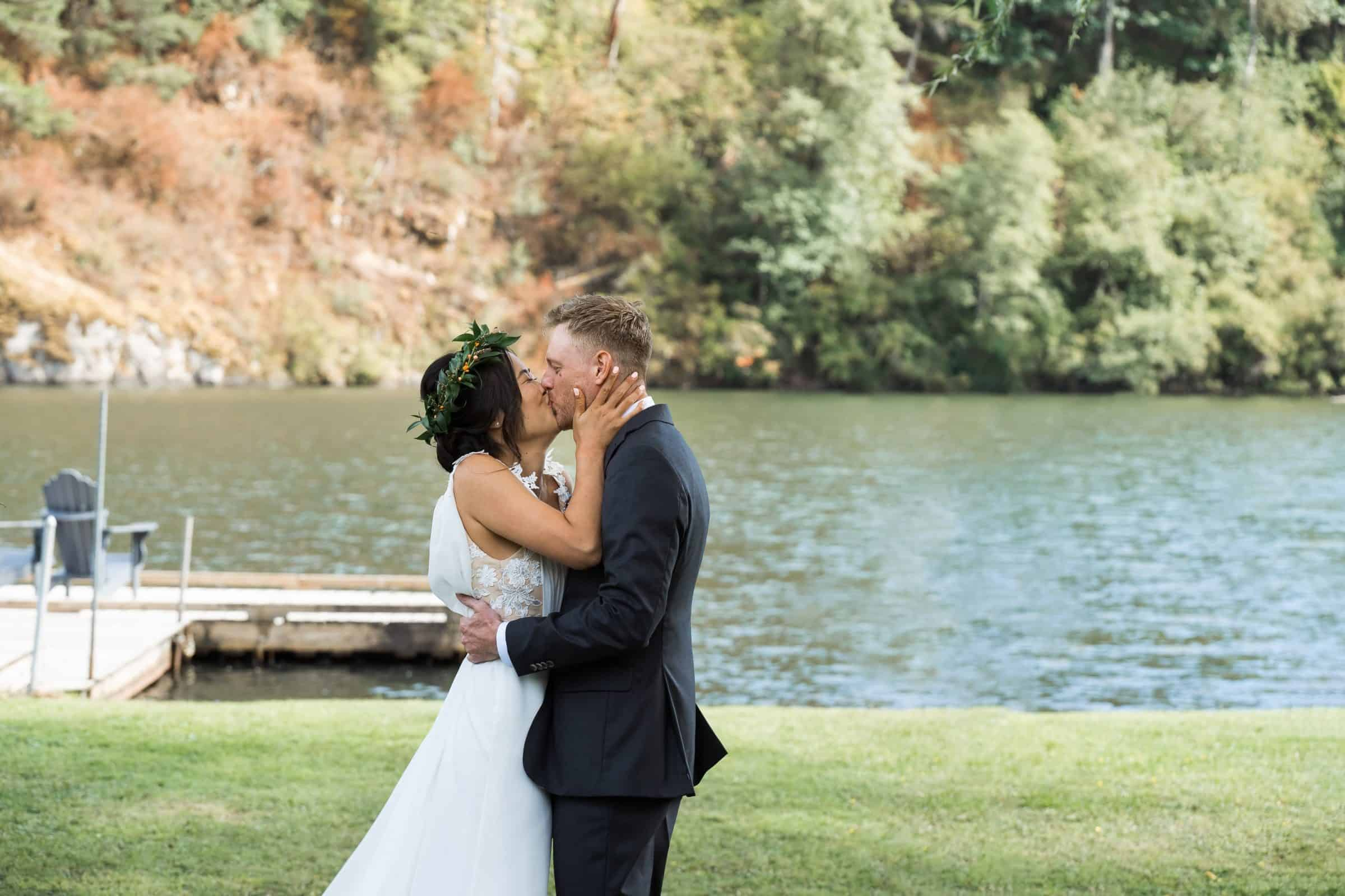 bride and groom first kiss with lake in the background