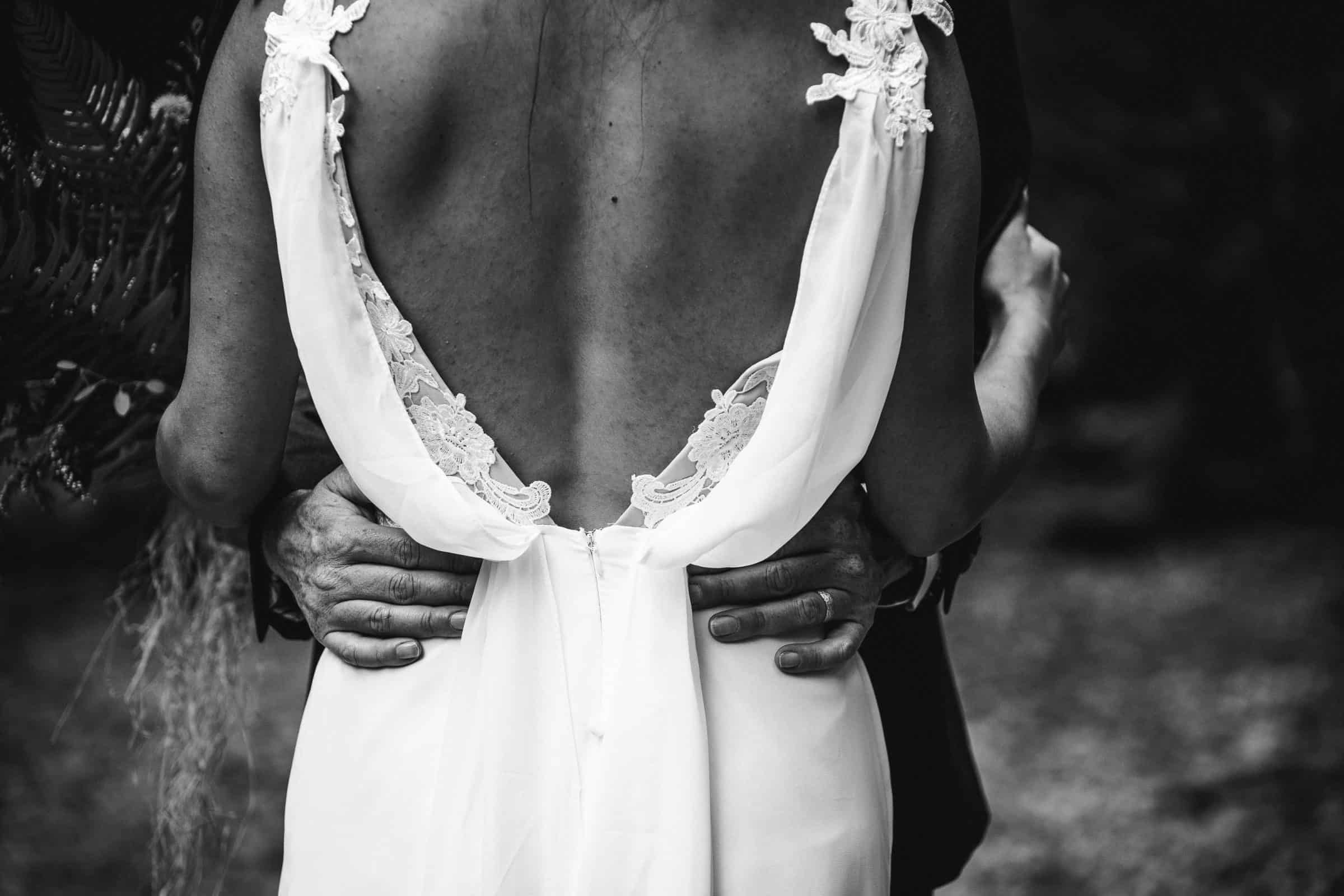 close up of groom's hands on bride's hips