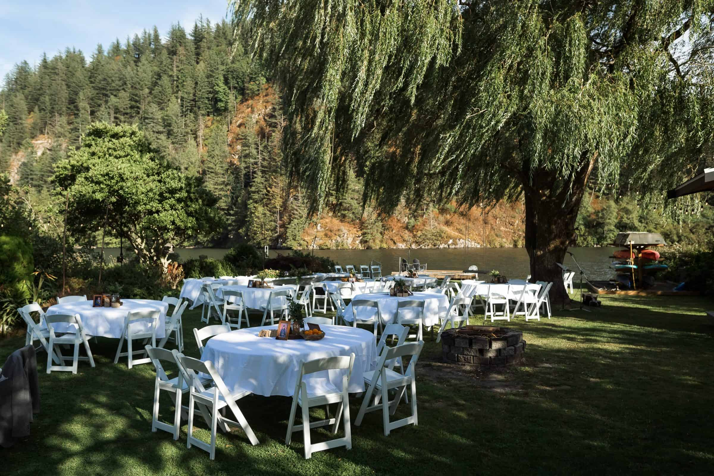 pull back of tables set up for wedding reception in backyard by lake