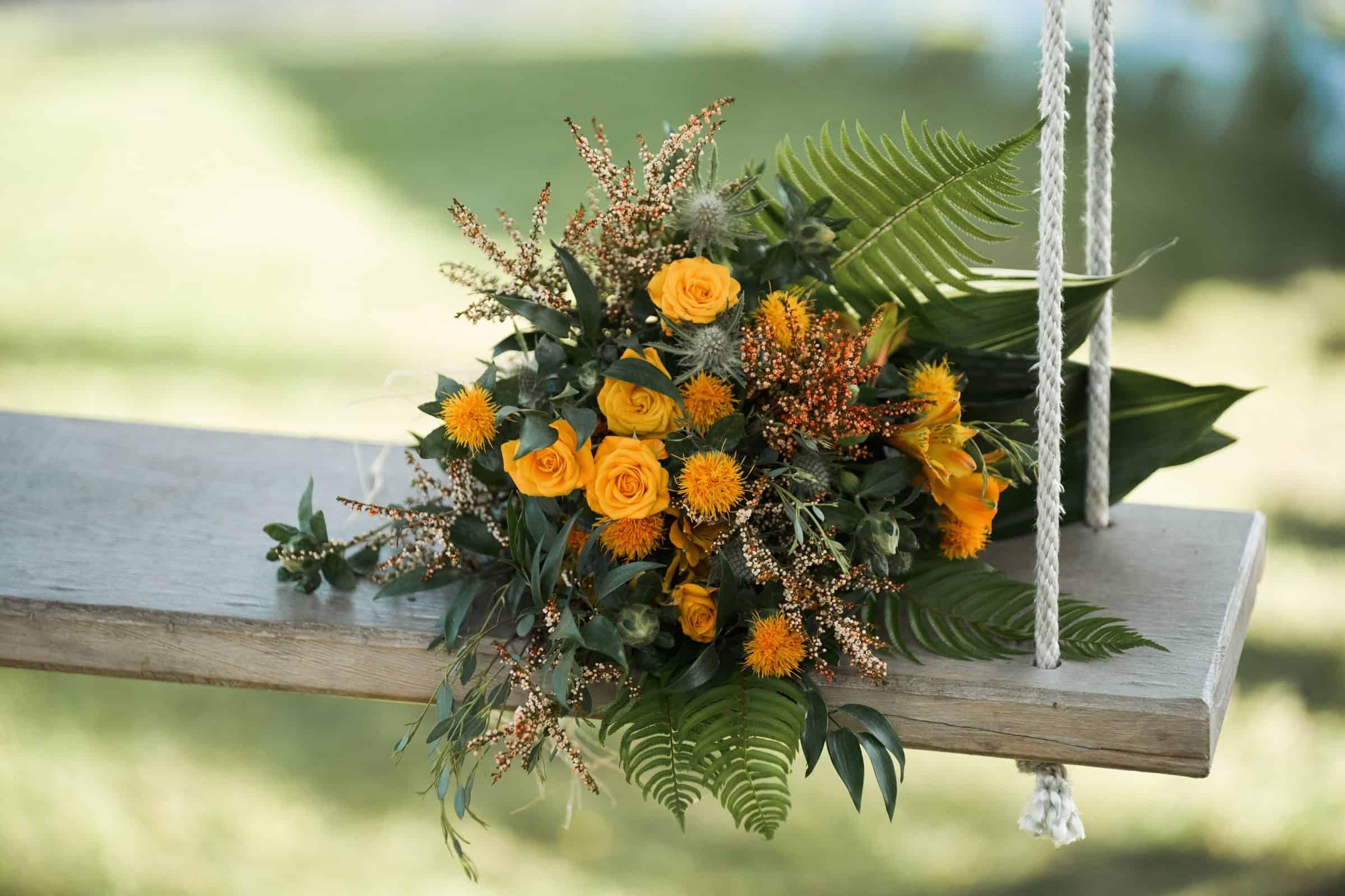 bridal wedding bouquet sitting on wooden swing