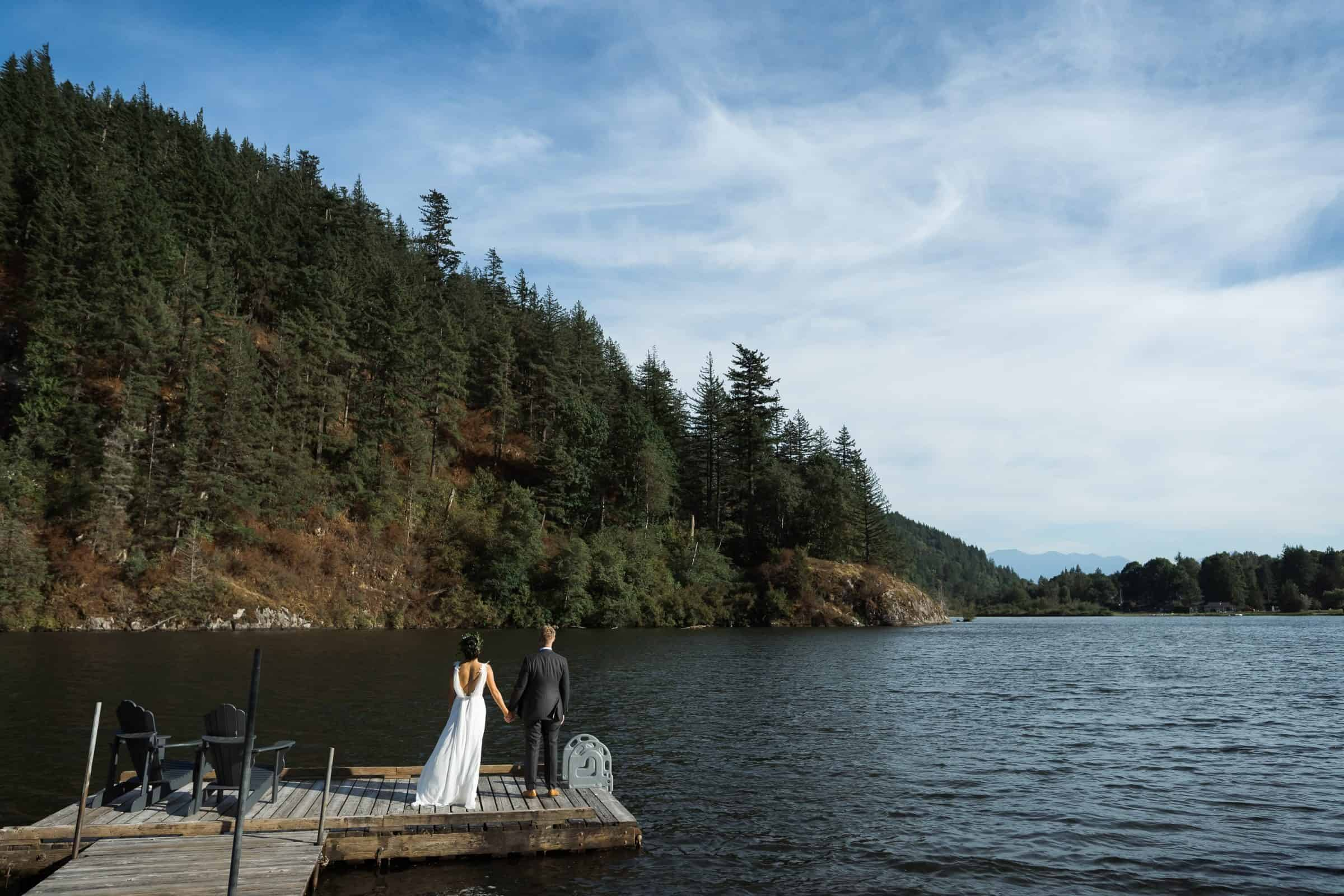bride and groom standing on a dock by lake and mountains at sunset