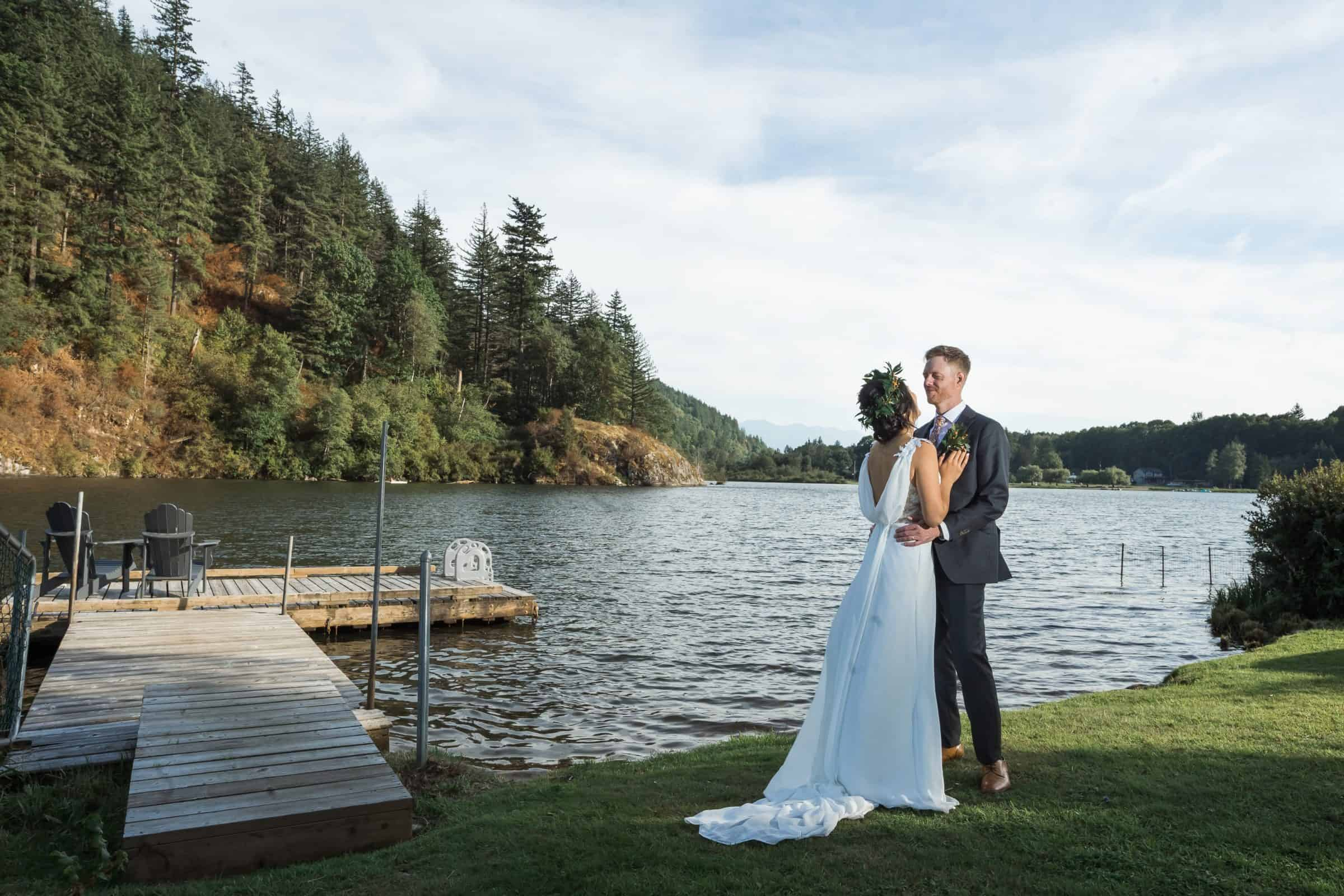 bride and groom standing beside a dock and lake at sunset