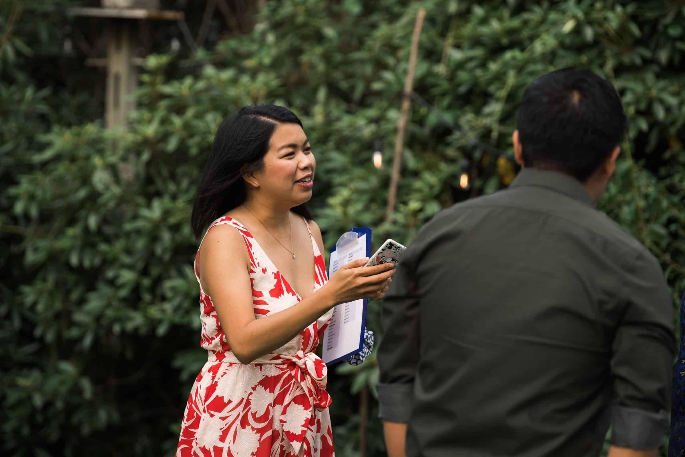 close up of guest helping organize people at backyard wedding