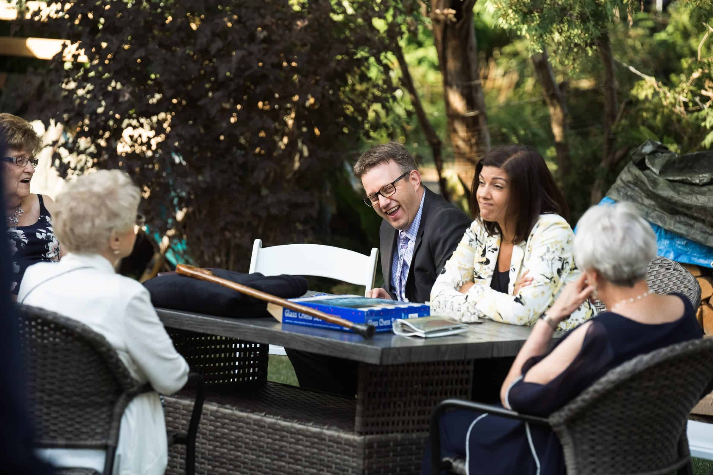 people laughing and conversing at table in backyard