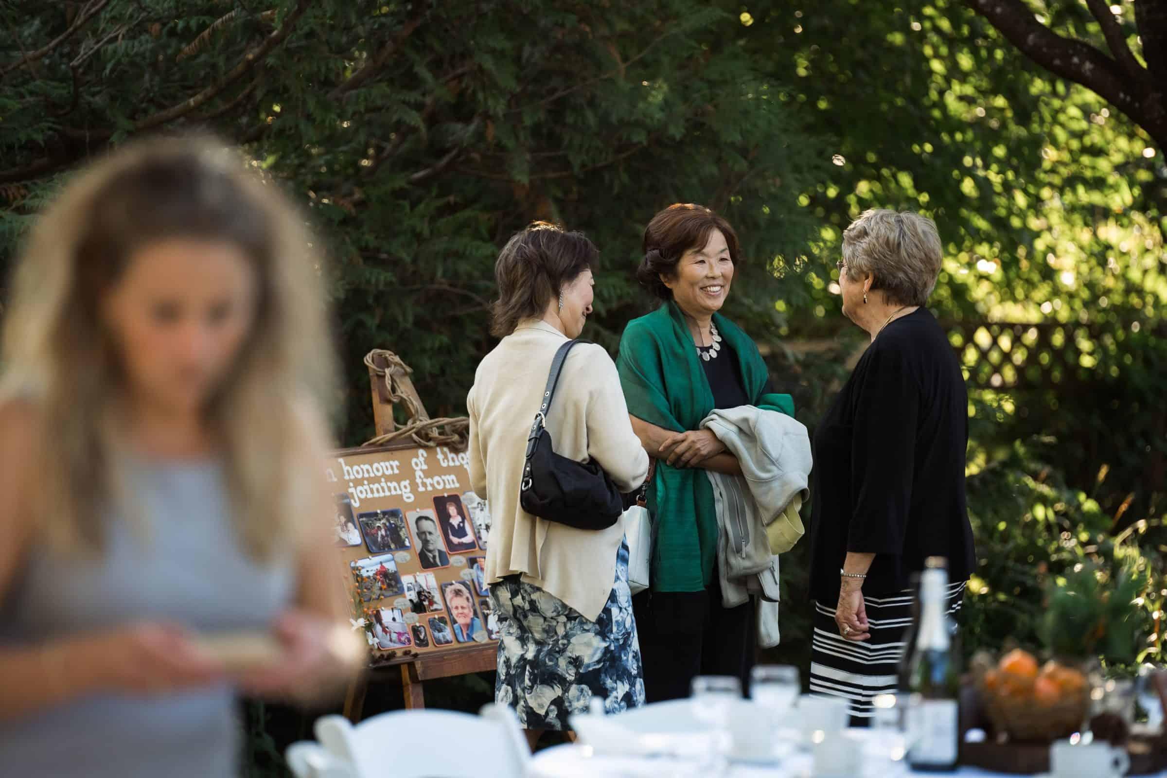 ladies smiling and talking in backyard at wedding