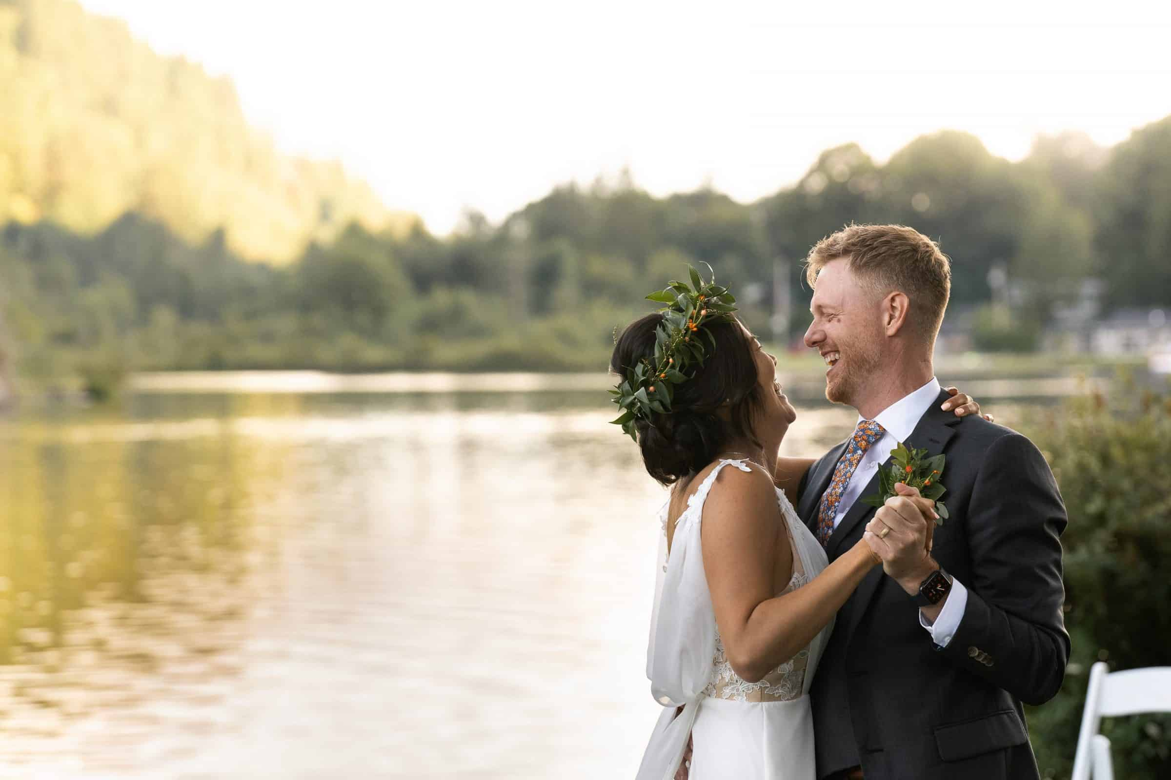 bride and groom dancing at sunset by lake and laughing