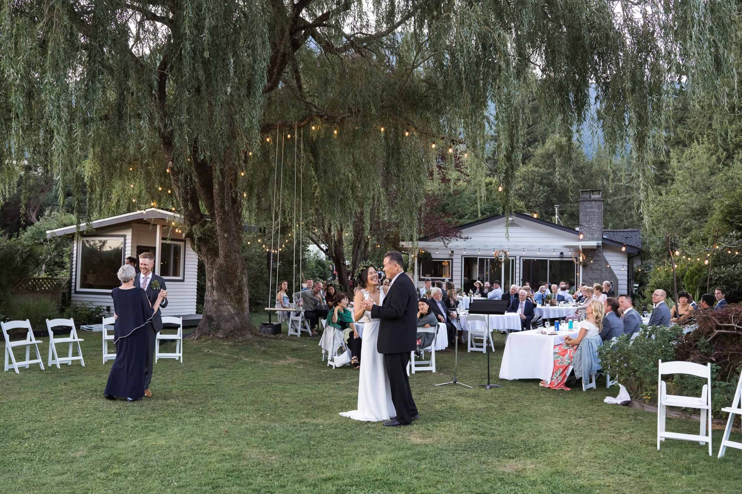 mother-son and father-daughter dances at wedding with guest in background in yard