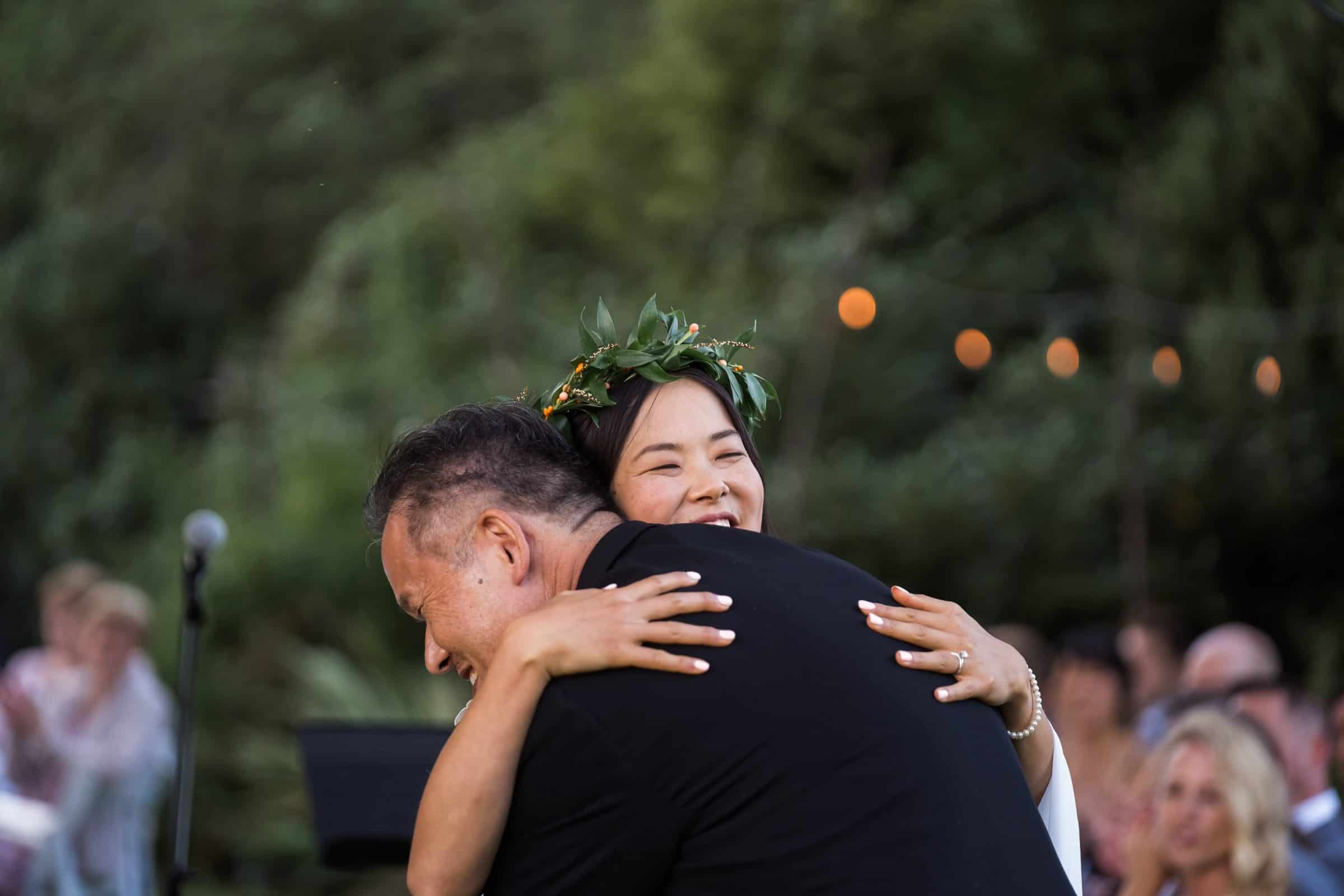 bride hugging father and laughing