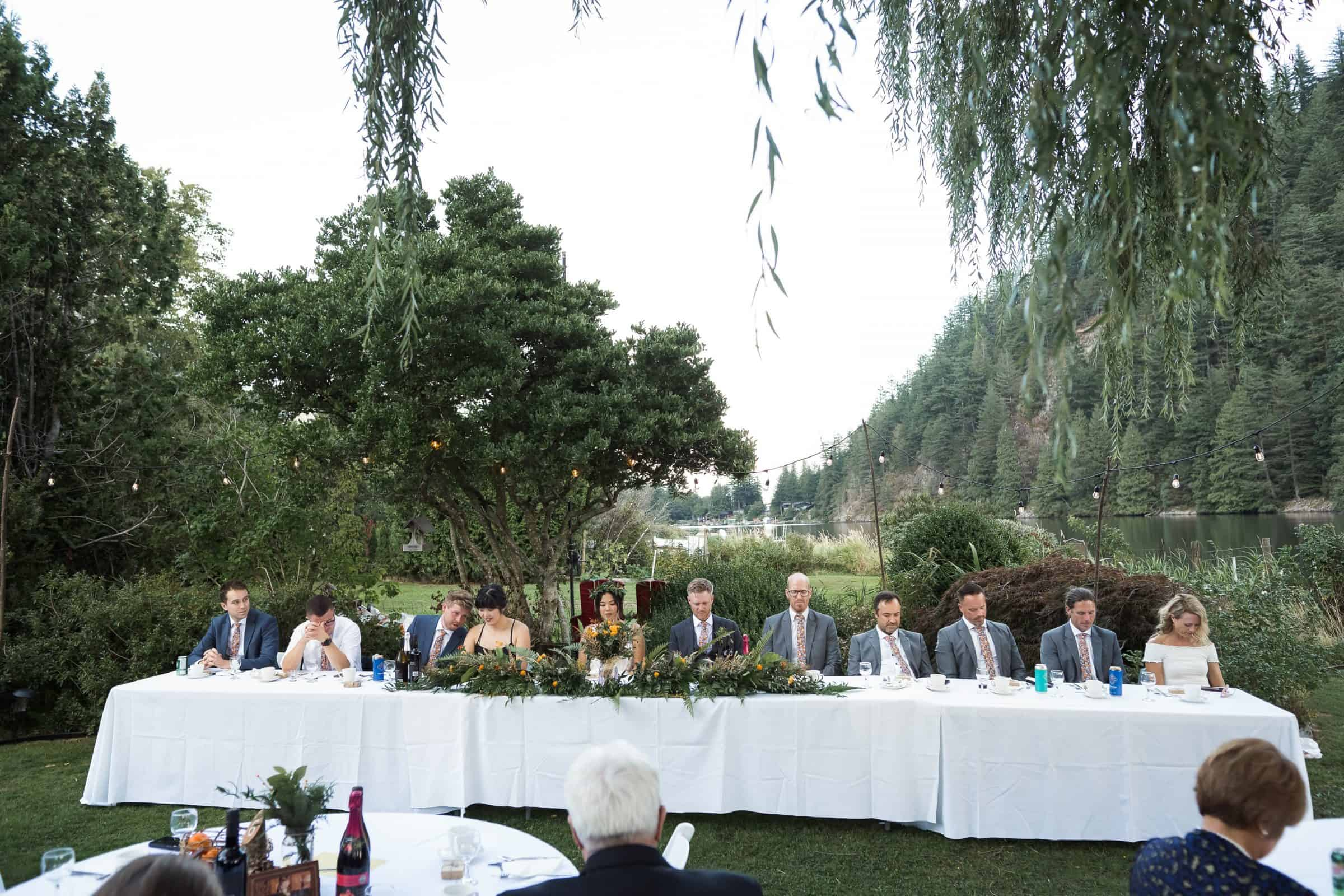 wedding head table in backyard by lake with bridal party sitting at it
