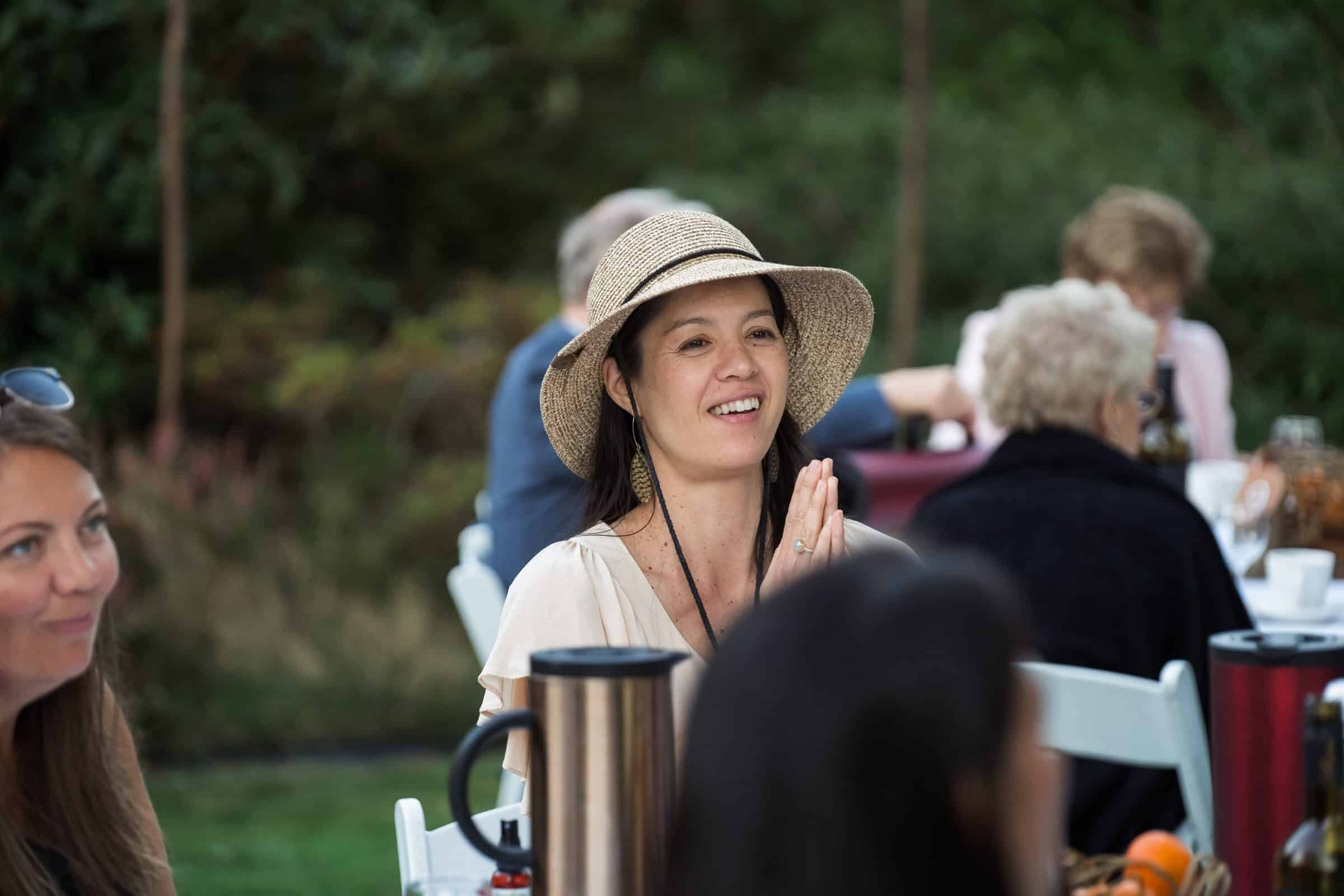guest in hat clapping at wedding reception