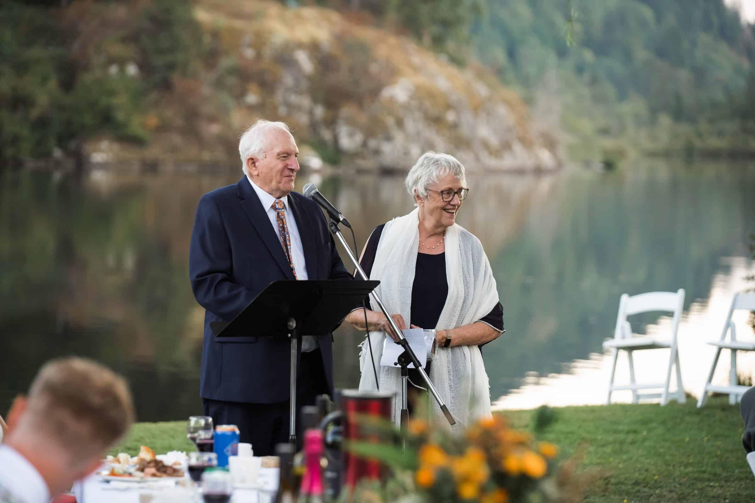 groom's parents giving speech beside lake