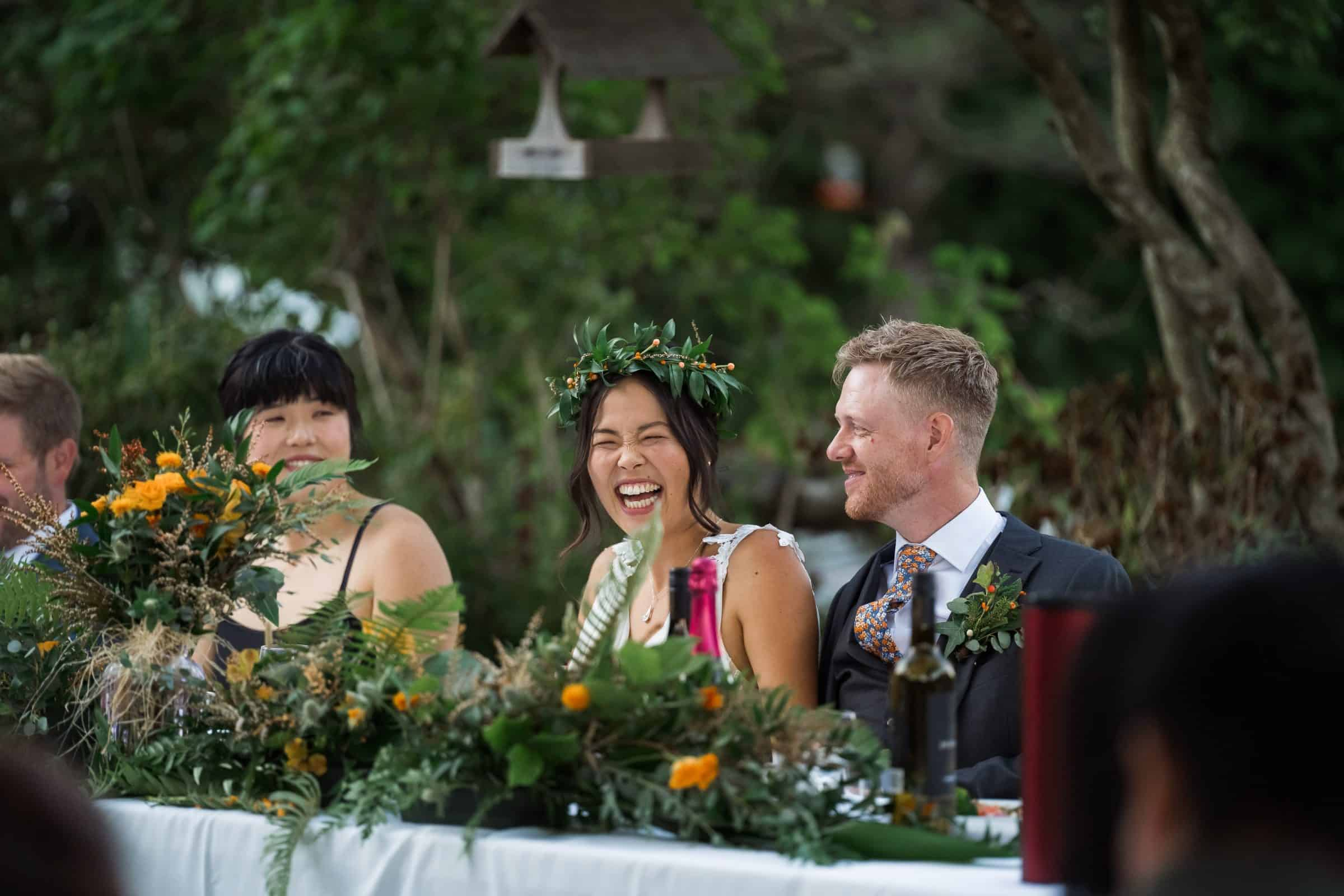 bride and groom laughing at head table