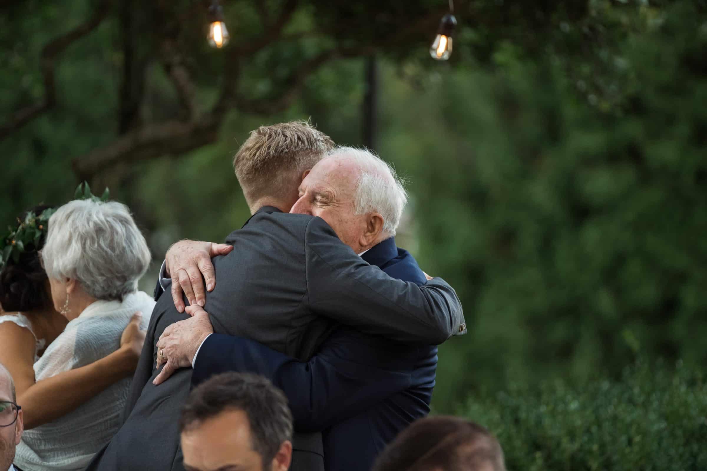 groom and bride hugging parents