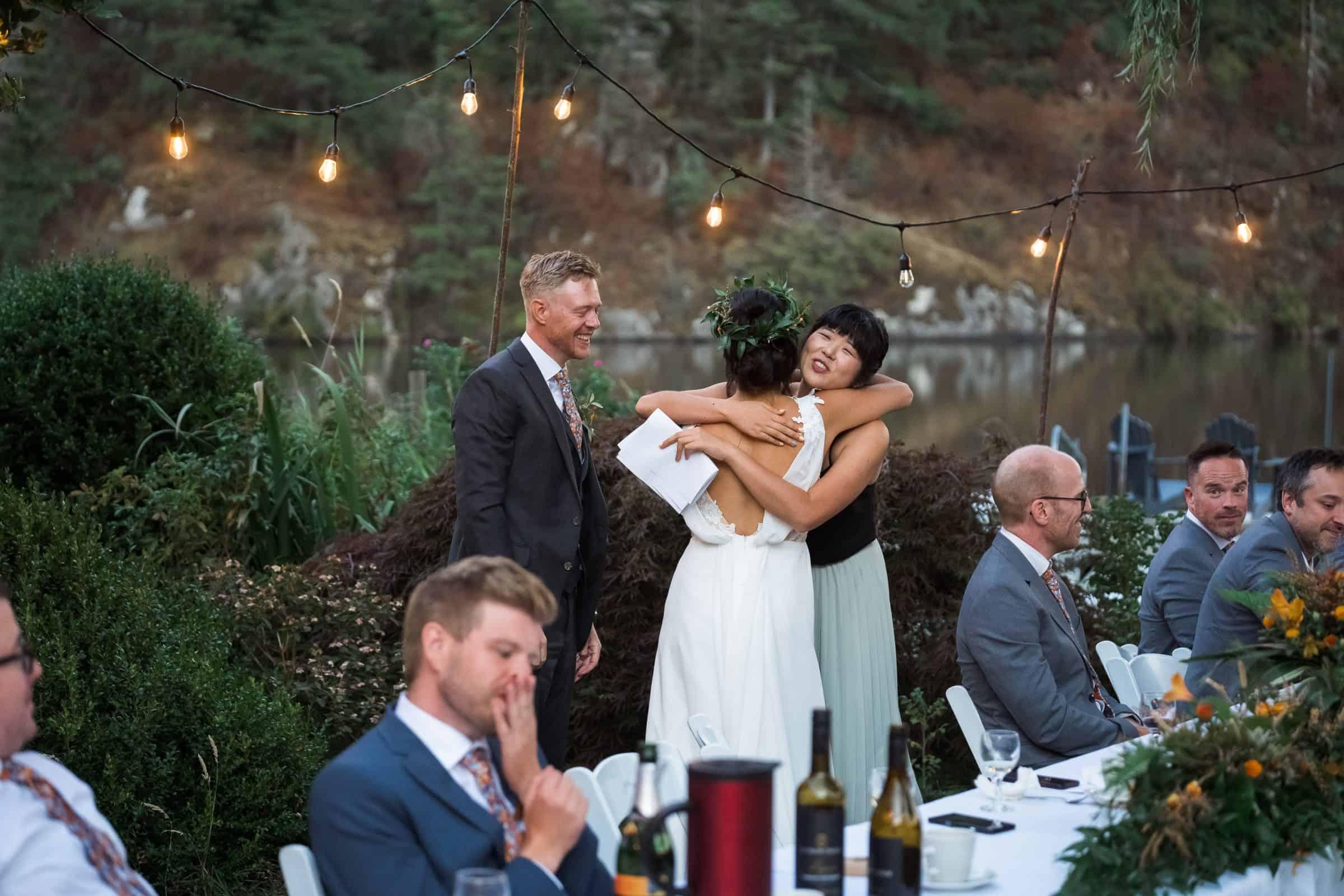 bride hugging maid of honour at head table at wedding
