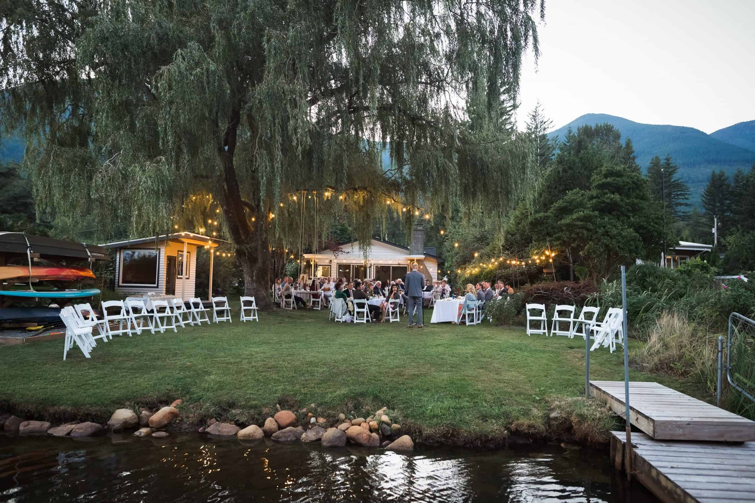 pull back of backyard wedding venue under trees and lights