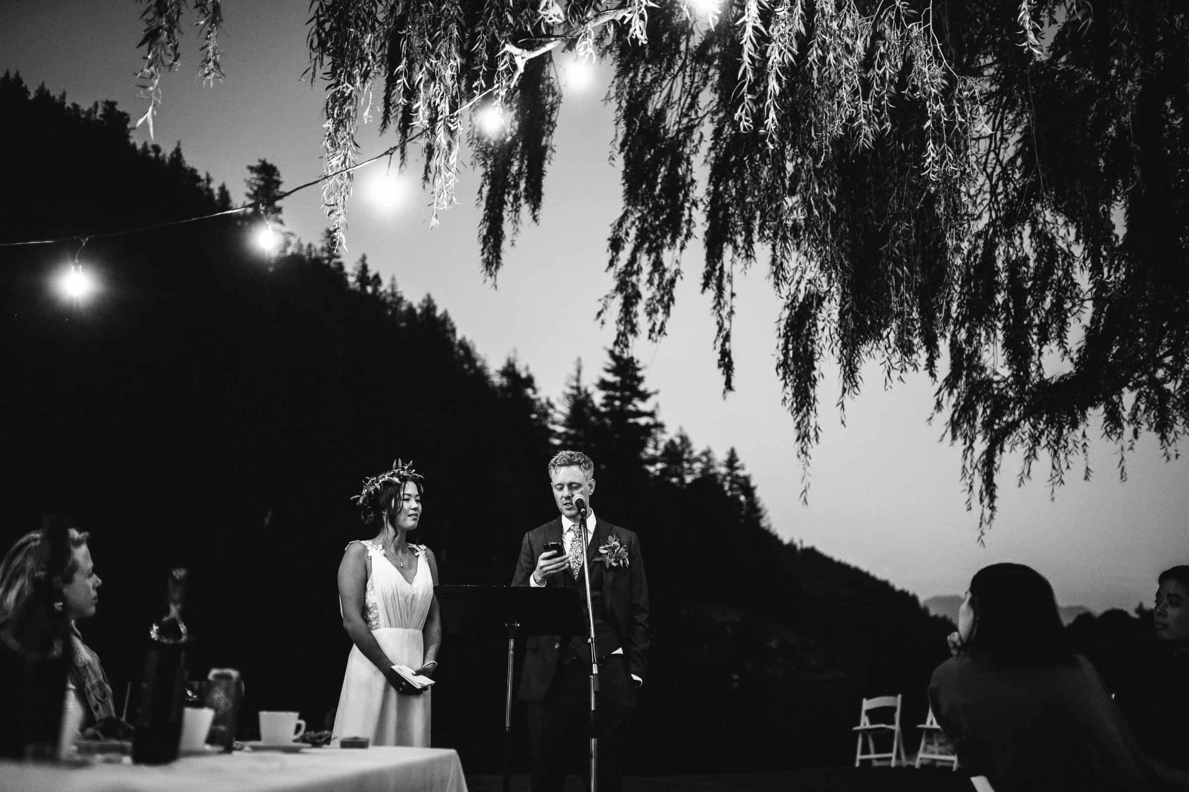 black and white image of bride and groom giving speech under trees and lights